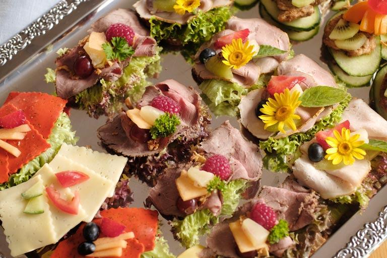 Detail einer liebevoll garnierten kalten Platte mit Kochschinken und Schweinebraten von Partyservice Rode